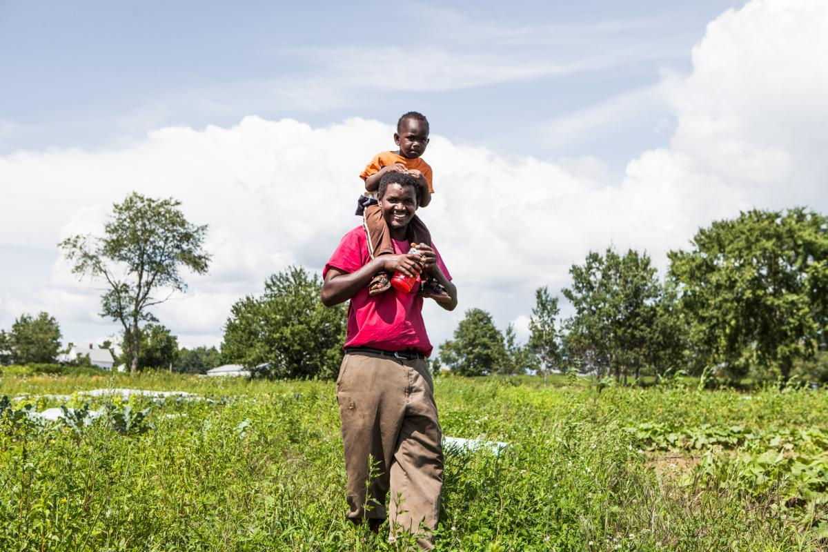 Hussein Muktar with a child on his shoulders in the field